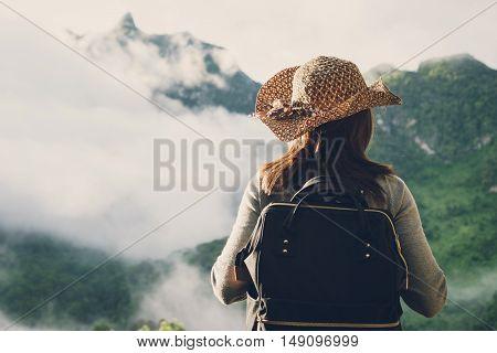 Woman traveler looking fog on the mountain Vintage tone