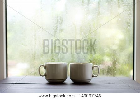 Two the light cup of coffee on a wooden table against the window after rainy weather / cozy atmosphere for coffee breaks