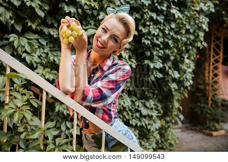 Cheerful beautiful young woman with red lips standing and holding bunch of grape