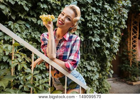 Cheerful cute pinup girl holding bunch of fresh grape outdoors