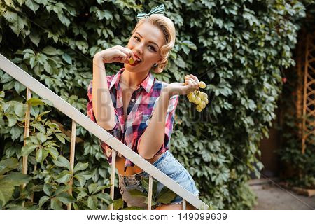 Cheerful attractive pin up girl standing and eating grape in the garden