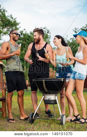 Group of cheerful young friends drinking beer and frying meet on barbeque grill outdoors
