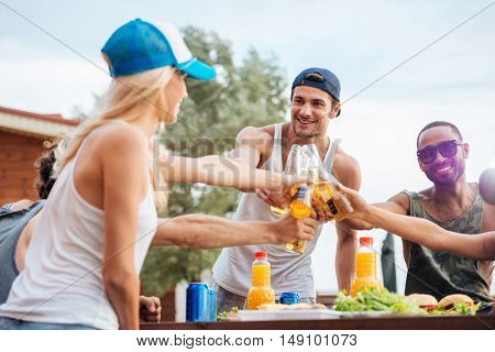 Group of cheerful young friends drinking beer and celebrating outdoors