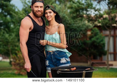 Portrait of beautiful young couple standing near barbeque grill outdoors