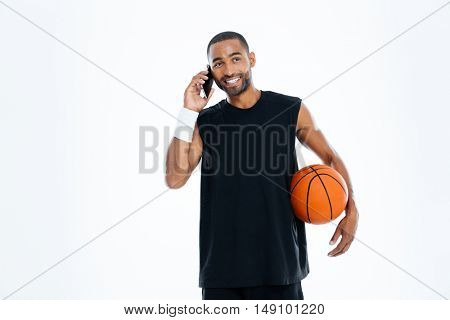 Happy african young basketball player talking on mobile phone isolated on a white background