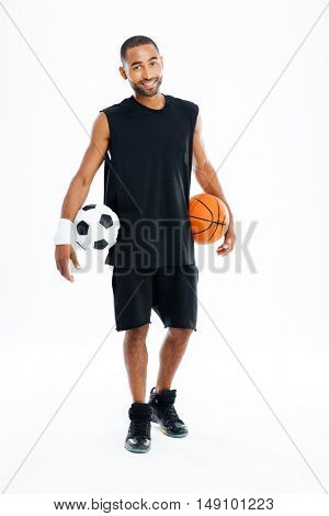 Cheerful african sports man holding basketball and soccer ball isolated on a white background