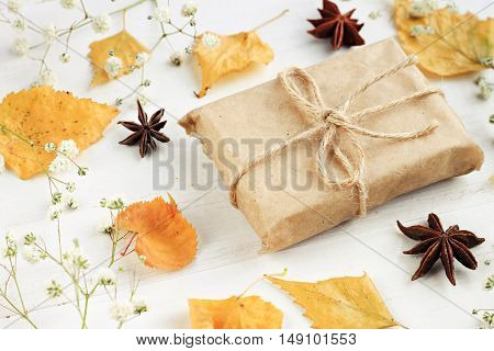 Autumn eco-craft. Handmade gift paper wrapping, dried fall leaves decor arrangement, light background.