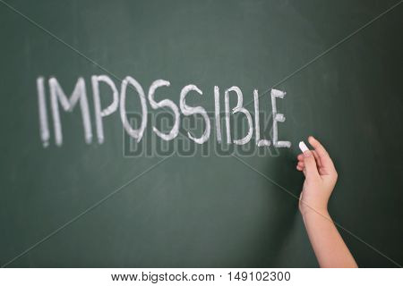 Little girl writing word impossible on chalkboard