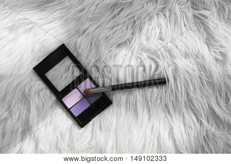 Eye shadows palette and brush on fluffy carpet background