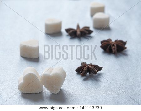 Sweet hearts and anise stars upon shiny blue background. Selective focus on the front.