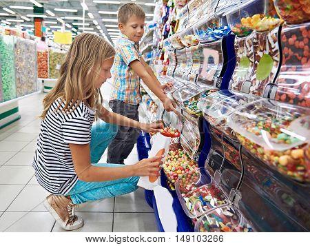 The children buy gummi candy in shop