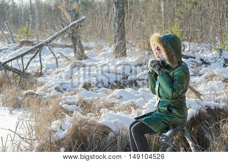 Young woman is taking break in winter snowy forest outdoors
