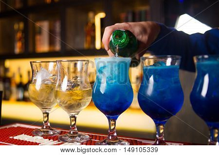 an alcoholic colored cocktails is in beautiful glass,pours in the restaurant