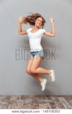 Full length portrait of a cheerful woman jumping and showing v gesture isolated on a gray background