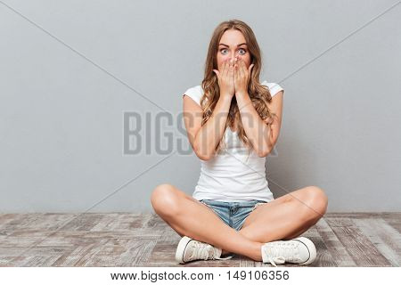 Young woman covering her mouth with palm while sitting on the floor isolated on a gray background