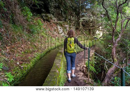 Young woman tourist with backpack and gps navigation equipment doing her hike at Rabacal's levada 25 fountains. Madeira island, Portugal.