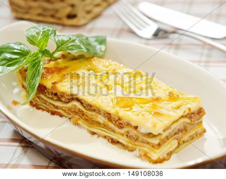 Close-up Of A Traditional Lasagna Made With Minced Beef Bolognese Sauce Topped With Basil Leafs Serv