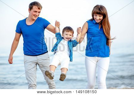 Woman and man tossed the boy up behind Ocean and clean sandy beach