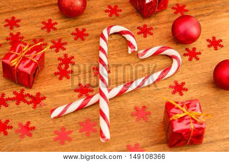 Christmas candy canes with heart shape on a wooden background