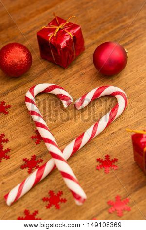 Candy canes with Christmas balls on a wooden background. Xmas decoration
