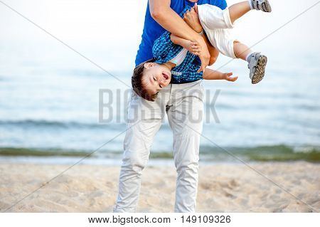 Men shakes a boy on the sea and have fun on a bright sunny day