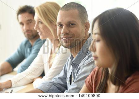 Smiling hispanic businessman attending meeting