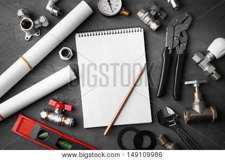 Notebook and plumber tools with blueprints on concrete structure background