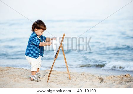 A child on the beach draws by paint on the easel on the beach