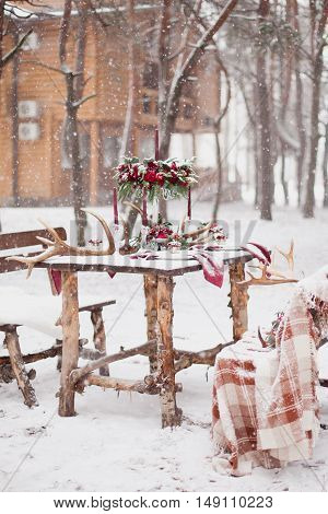 Table Made Of Pine In Snowbound Forest In Winter With Red Wedding Table Setting. Winter Decoration C