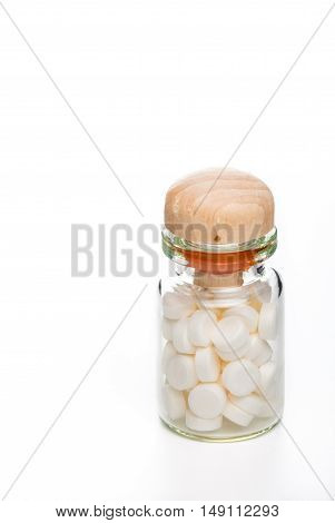 White pills in clear glass container with wooden top on white background