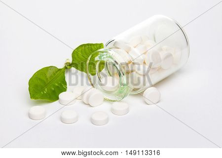 White pills in clear glass container with green leaf on white background