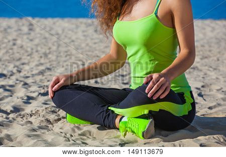 Young slim girl in black and light green tracksuit sitting after a workout in the sand on the seashore. The concept of a healthy lifestyle and body care.