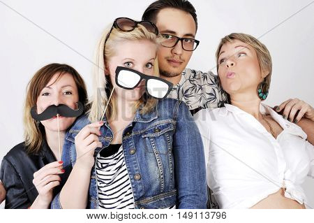 Happy smiling young group is joking with artificial mustache and paper glasses. isolated on white background.