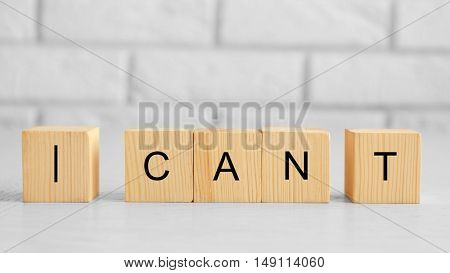 Wooden cubes with phrase I CANT on brick wall background