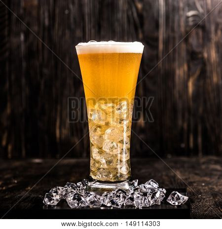 glass of light beer with ice and head of foam on dark wooden background