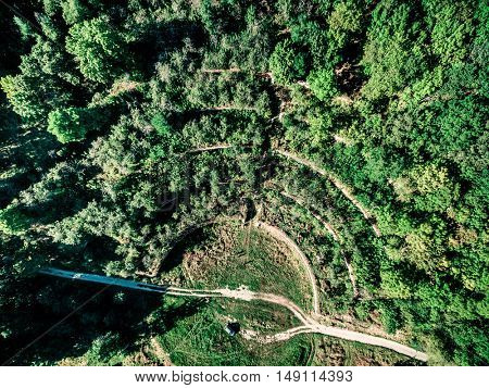 beautiful lush green forest with hills and crossing track, top view