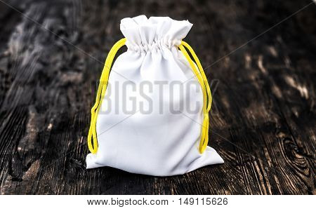 white little fabric gift sac with yellow ties on dark wooden background