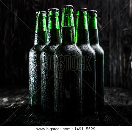 Green bottles with beer on black background