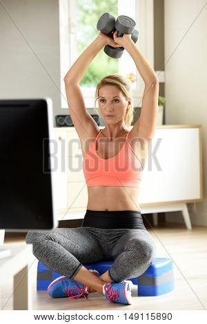 Fitness girl lifting dumbbells in front of TV program