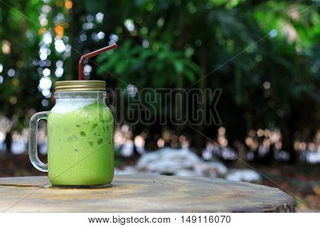 ice green tea on wood table and tree background