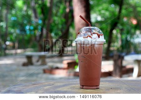 ice chocolate on table and tree background