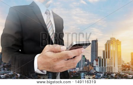 Businessman using mobile phone with cityscape of Bangkok city in sunrise