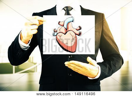 Businessman holding card with creative realistic heart sketch on blurry background. Health concept