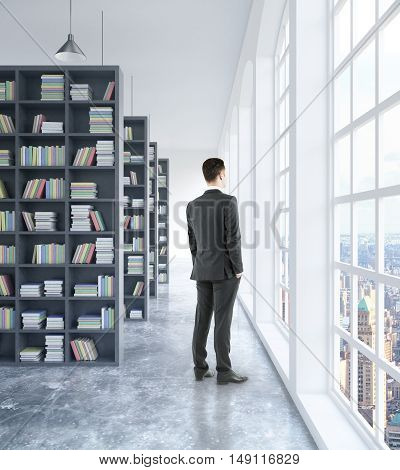 Businessman looking out of window in modern concrete library interior with book shelves daylight and city view. 3D Rendering