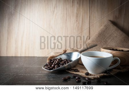 Coffee cup with coffee bean on black stone background