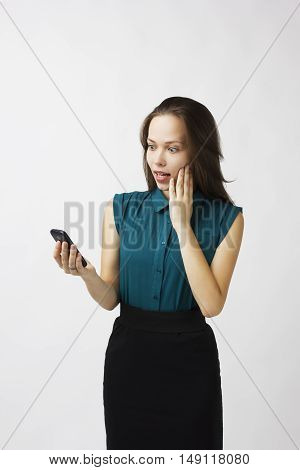 business woman with astonishment looks at the phone on a white background