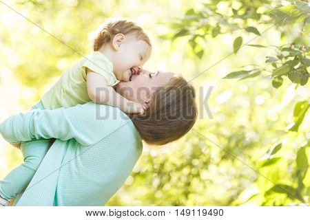 Young mother holds little girl in summer park