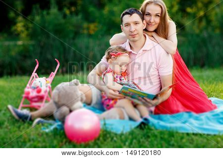 Happy family with little daughter sitting in park on blanket with toys