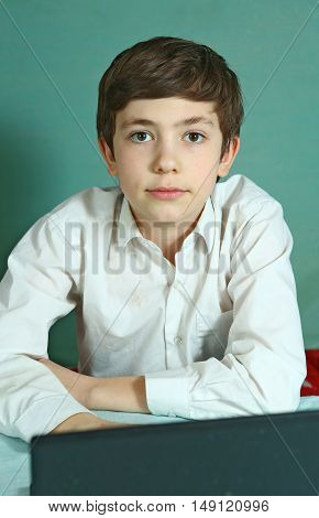 preteen handsome boy with laptop before online lesson