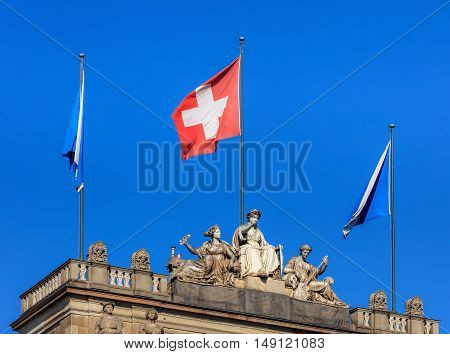 Zurich, Switzerland - 25 September, 2016: upper part of the Zurich Main Railway station building with sculptures and flags of Zurich and Switzerland. Zurich Main Railway station is the largest railway station in Switzerland.